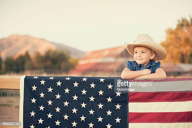 Junge amerikanische Cowgirl mit US-Flagge