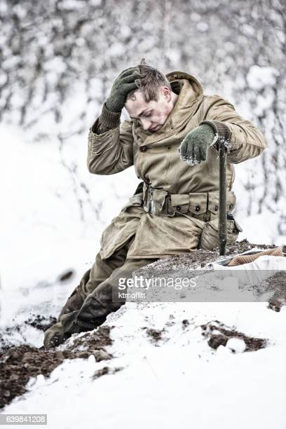 Young American GI In WWII Worn Out Digging Winter Foxhole