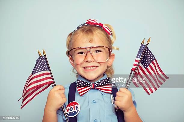 Young American Girl Holding Flags en las urnas
