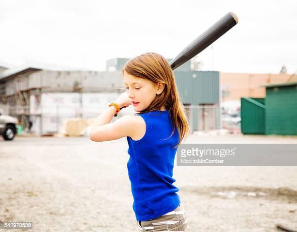 Jeune fille pratiquant le base-ball américain swing dans un cadre urbain