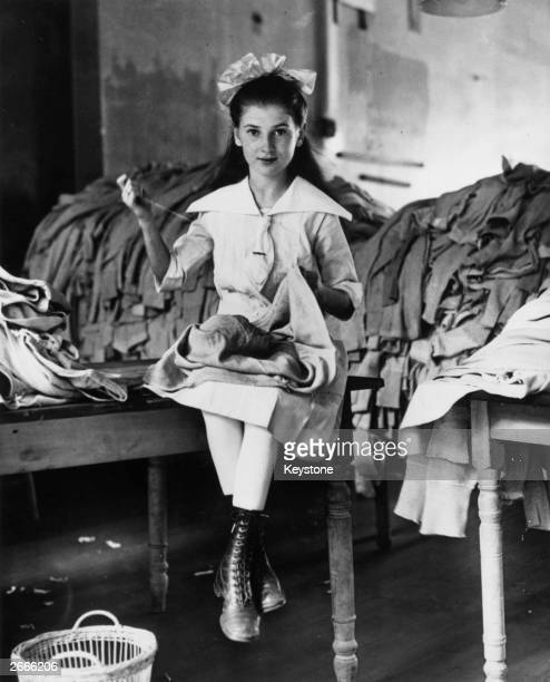 A young American girl repairing army uniforms during the First World War