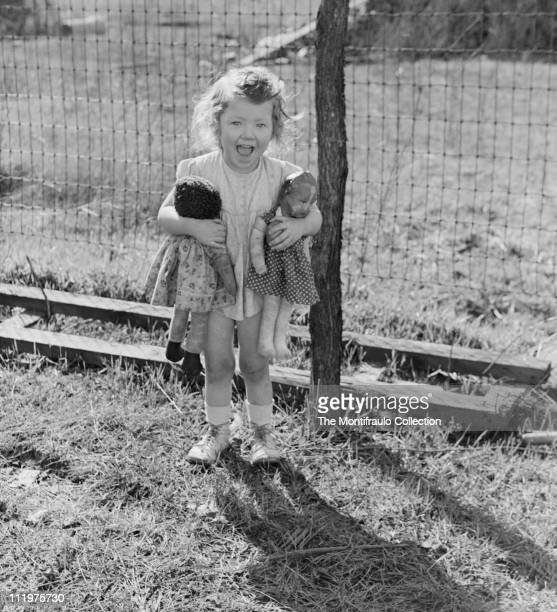 Young American girl wearing a short summer dress and holding two well loved rag dolls tightly in her arms posing in her backyard circa 1946