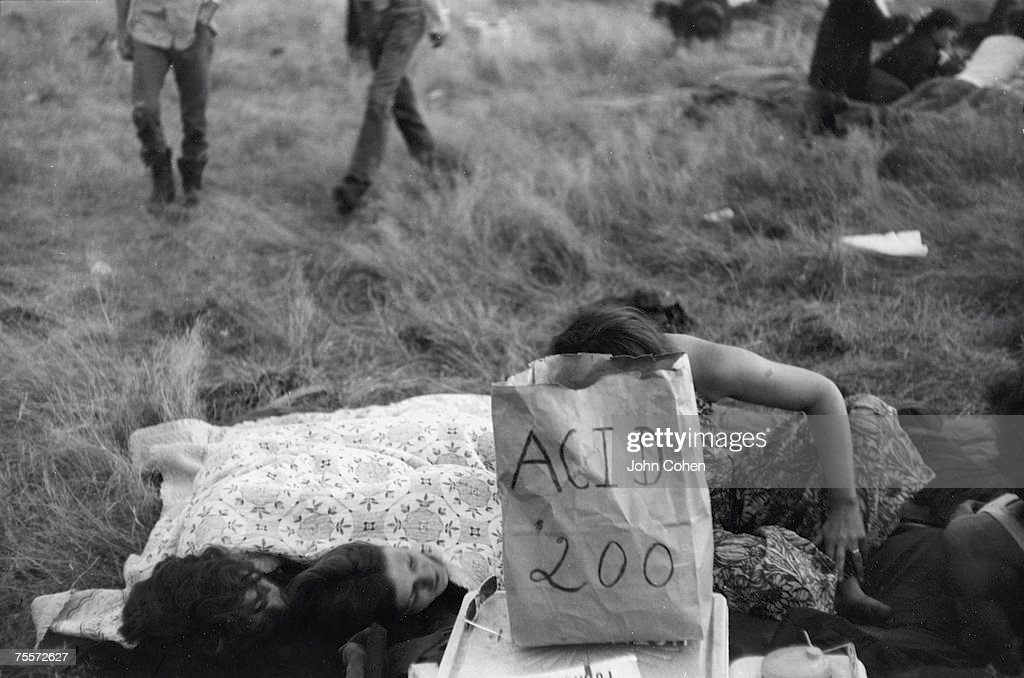 Young American hippies sit and lie on the grass as they wait for customers who wish to purchase Lysergic acid diethylamide (or LSD) from a paper sack labelled 'Acid $2.00' at the second Sky River Rock Festival and Lighter Than Air Fair, a rock music and ballooning event, near Tenino, Washington, late 1969.