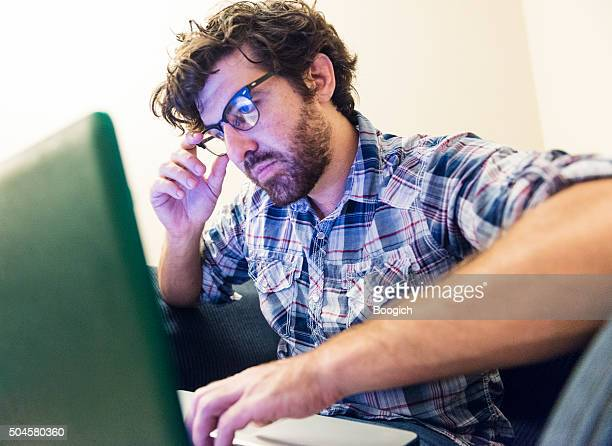 Young American with Beard Looks Serious Reading on Laptop Computer