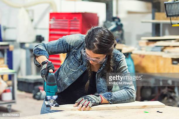 Young American woman cutting wood