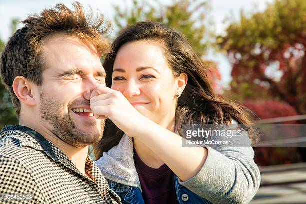 Young American woman teasing her boyfriend by pincing his nose