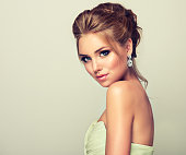 Beautiful woman dressed in evening gown. Example of wedding hairstyle for blond-haired ladies. Young and attractive blond model, straight look on camera. Trendy hairstyles, make up and outfit.