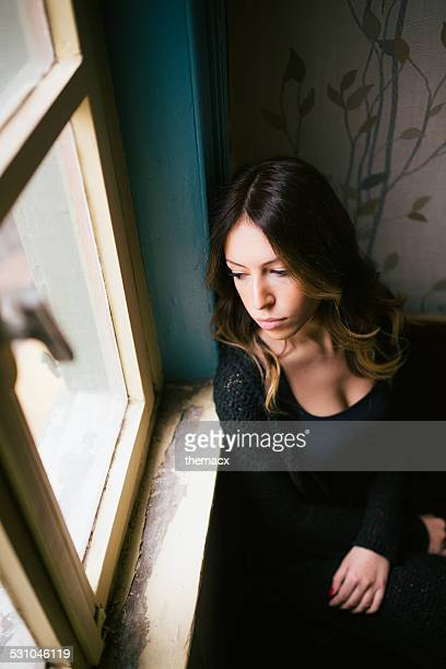 Young and attractive female looking through window