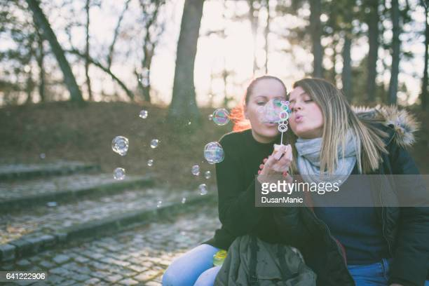 Young and beautiful girls blowing bubbles