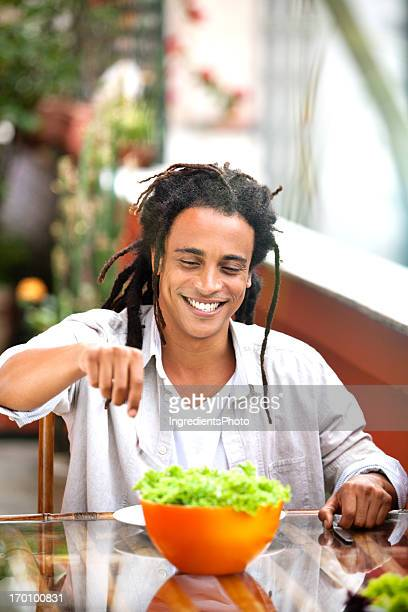 Young and beautiful smiling man eating salad on the table.
