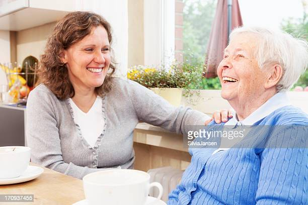 Young and elderly woman drink coffee and laugh