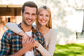 Beautiful young couple bonding to each other and smiling while standing against their new house