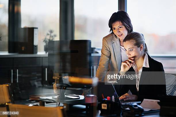 Young and Mature Business Woman Working Late
