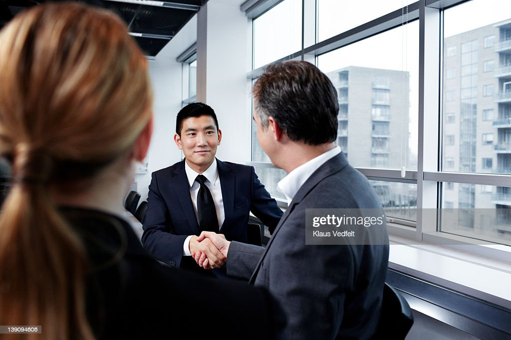 Young and mature businessmen making handshake : Stock Photo