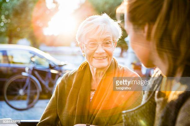 young and senior woman sit together in a sidewalk cafe