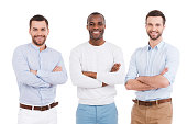 Three confident young men in smart casual wear keeping arms crossed and smiling while standing against white background