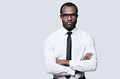 Handsome African man looking at camera and keeping arms crossed while standing against grey background