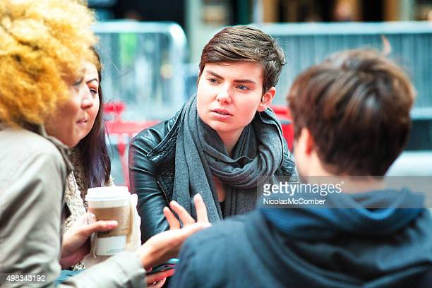 Young androgynous woman listens to friend with interest