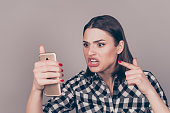 Young angry woman screaming at smartphone  while chatting with her boyfriend