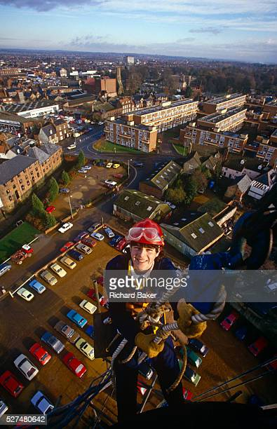 A young apprentice stop near the top of a city centre chimney during a steeplejack course in Kings Lynn Norfolk Using an elaborate system of...