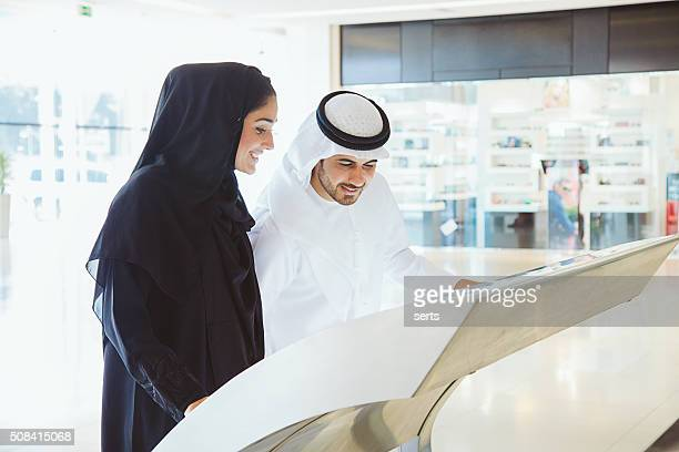 Young Arab couple using information display at mall