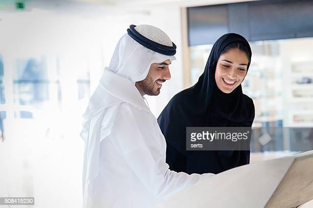 Young Arab couple using information display at mall