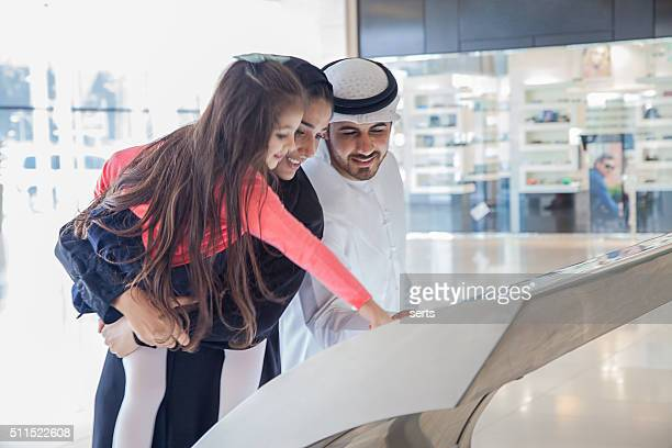 Young Arab family using information display at mall