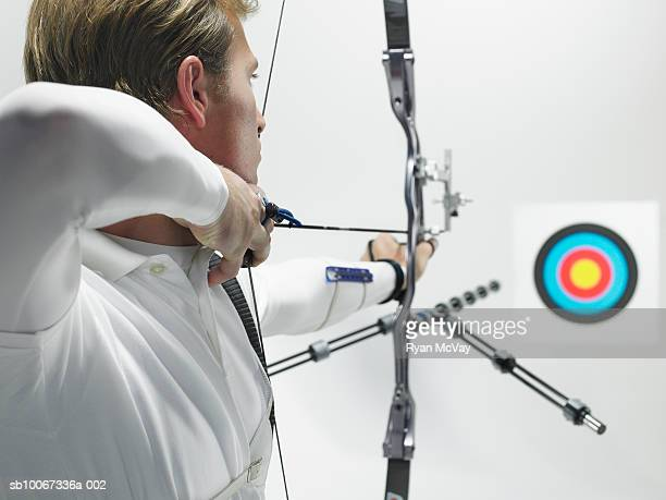 Young archer aiming at target, studio shot