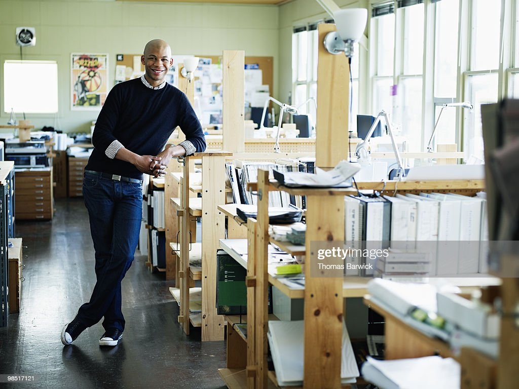 Young architect leaning on workstation in office : Stock Photo