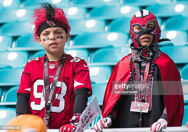 Young Arizona Cardinals fans wearing masks and wigs in the stands before the start of the NFL football game between the Arizona Cardinals and the...