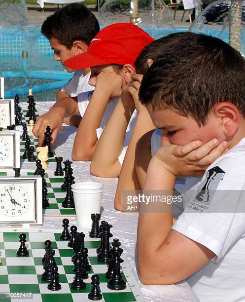 Young Armenian children play chess during a street tournament in Yerevan on July 29 2011 Armenia's top chess players lauded as heroes after winning...