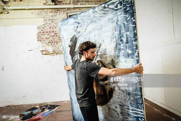 Young artist carrying big painting
