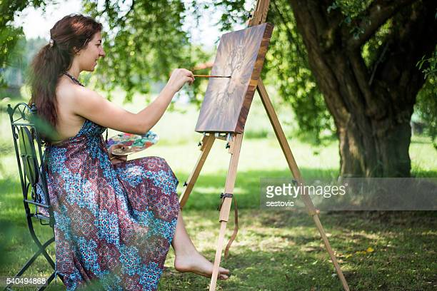 Young artist painting outside