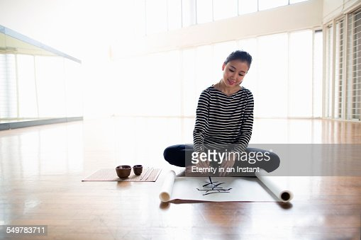 Young artist writing calligraphy in study