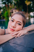 Young Asia woman happy in swimming pool.Resort in Thailand.
