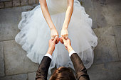 young asian newlywed couple wearing wedding dress dancing in open ground, high angle view.