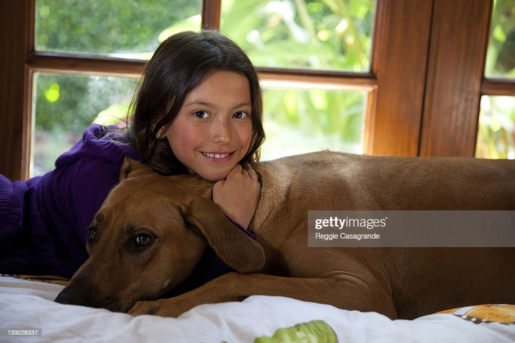 Young Asian American girl with her dog : Stock Photo