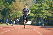 young asian man male athlete running training exercising on track, rear view.
