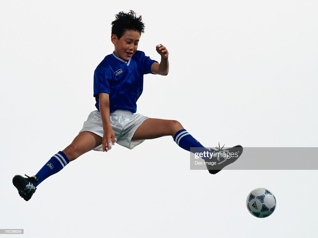 Young Asian boy kicking football in mid air : Stock Photo