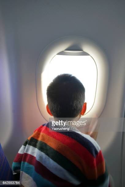 Young asian boy looking outside of the airplane window