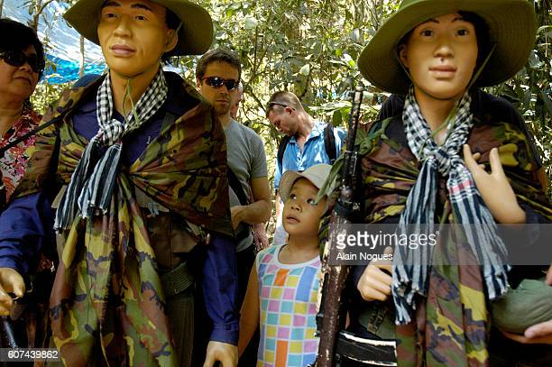 A young Asian boy looks at Vietcong mannequins dressed in urban guerilla warfare outfits at the War Remnants Museum in Cu Chi