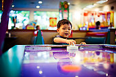 Young Asian boy playing air hockey game