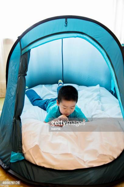 Young asian boy playing digital tablet in tent