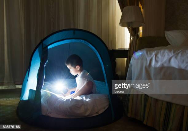 Young asian boy playing in tent