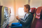 Young asian business man smiling and playing game with happinest in airplane