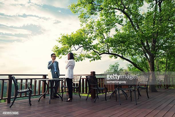 若いアジアビジネスの人々で話している屋外カフェ
