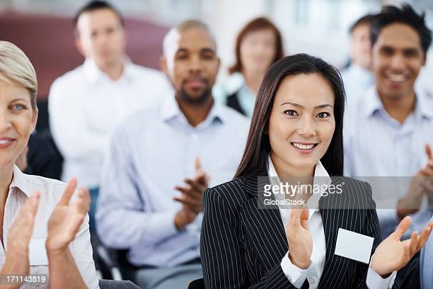 Young Asian business woman at a seminar applauding