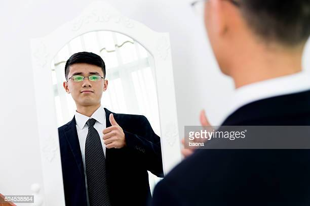 Young asian businessman checking his looks