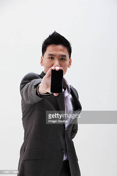 Young Asian businessman holding cellphone, studio shot