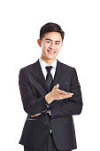 young asian businessman making an invitation, looking at camera smiling, isolated on white background.